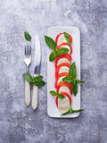 意大利caprese沙拉用无盐干酪、蕃茄和蓬蒿 库存图片