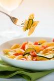 意大利penne面团用夏南瓜和西红柿 免版税库存图片