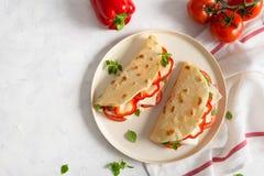 意大利piadina romagnola小面包干用红辣椒、蕃茄、意大、乳酪和蓬蒿在板材在白色木 库存图片