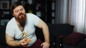意志薄弱的超重食人的薄饼和饮用的啤酒坐长沙发 营养不良,体育,肥胖病的概念 股票视频