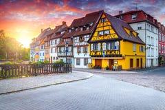 意想不到的中世纪半木料半灰泥的门面和被铺的街道,科尔马,法国 免版税库存照片