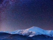 意想不到的冬天流星雨和积雪覆盖的山 免版税库存图片