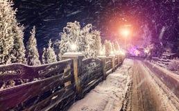 意想不到的冬天,夜场面 在村庄的雪风暴 冷淡的夜间 库存照片