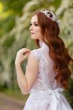 意想不到的婚礼礼服的美丽的红头发人新娘在开花的庭院里 免版税库存图片