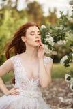 意想不到的婚礼礼服的美丽的红头发人新娘在开花的庭院里 免版税库存照片