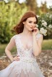 意想不到的婚礼礼服的美丽的红头发人新娘在开花的庭院里 库存图片