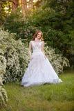 意想不到的婚礼礼服的美丽的红头发人新娘在开花的庭院里 库存照片