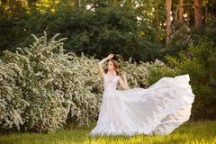 意想不到的婚礼礼服的美丽的红头发人新娘在开花的庭院里 图库摄影