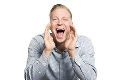 激动的年轻商人呼喊的了不起的新闻。 免版税库存照片