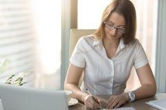 满意的女实业家签合同在书桌 库存照片