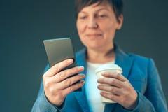 满意的看起来女实业家饮用的咖啡去和流动 免版税库存照片