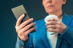 满意的看起来女实业家饮用的咖啡去和流动 库存图片