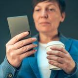 满意的看起来女实业家饮用的咖啡去和流动 库存照片