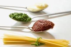 意粉和三把匙子用不同的调味品 库存图片