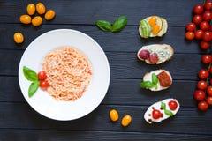 意粉和开胃菜bruschettas用蕃茄,三文鱼,奶油 免版税库存图片