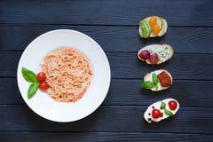 意粉和开胃菜bruschettas用蕃茄,三文鱼, crea 免版税库存图片