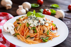 意粉意大利面制色拉用西红柿酱,蘑菇,青纹干酪 库存照片
