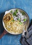 意粉用在一个生铁长柄浅锅的乳脂状的蘑菇在蓝色背景,顶视图 库存图片