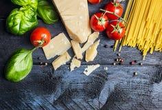 意粉的成份用西红柿酱:蓬蒿,蕃茄,在蓝色木背景,顶视图的巴马干酪 免版税库存照片