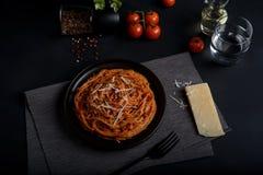 意粉面团用西红柿酱、新鲜的蕃茄和乳酪在黑暗的背景 免版税库存照片