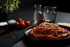 意粉面团用西红柿酱、新鲜的蕃茄和乳酪在黑暗的背景 免版税库存图片