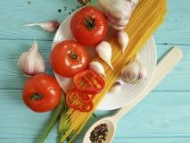意粉,蕃茄,大蒜在蓝色木背景的板材菜 免版税库存图片