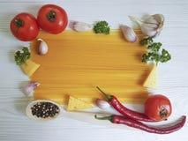 意粉,蕃茄,大蒜,胡椒厨房在白色木背景的乳酪菜单,烹调 免版税图库摄影