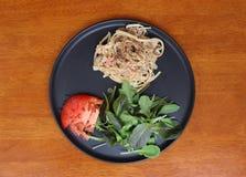 意粉Carbonara用绿色菜和红色蕃茄切开了成在黑盘的片断 库存图片