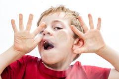 愚蠢小男孩使用傻,接触他的面孔和手 免版税库存图片