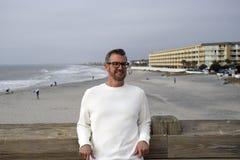 愚蠢海滩南卡罗来纳, 2018年2月17日-穿长的白色衬衣的白色男性模型倾斜反对与海滩的码头栏杆 免版税库存图片