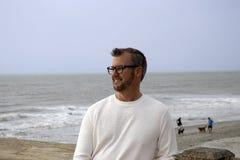 愚蠢海滩南卡罗来纳, 2018年2月17日-穿长的白色衬衣的白色男性模型调查与海洋wav的距离 免版税库存图片