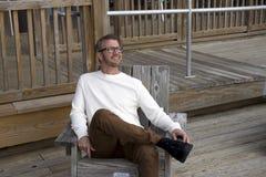 愚蠢海滩南卡罗来纳, 2018年2月17日-穿长的白色衬衣的白色男性模型,当放松在木甲板时的椅子, 免版税库存照片