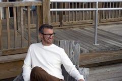 愚蠢海滩南卡罗来纳, 2018年2月17日-穿长的白色衬衣的白色男性模型,当放松在木甲板时的椅子 免版税库存照片