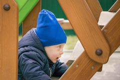 感兴趣的在操场的男孩走的台阶 免版税库存照片