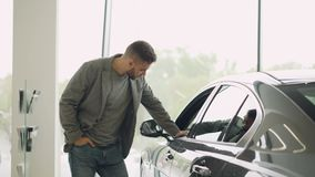 感兴趣的顾客在马达陈列室里检查美丽的汽车,看汽车并且接触它 在发光的焦点 影视素材