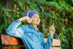 感到令人敬畏 凉快的质朴的女孩享受在室外的耳机的音乐 女孩在公园听音乐 曲调声音和mp3 免版税库存图片