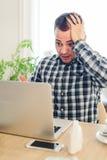 感到十分厌倦 沮丧的年轻人对负顶头在手上,当看对运转的膝上型计算机咖啡馆时 免版税库存图片