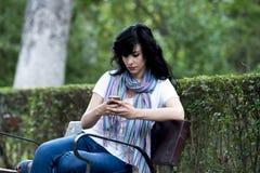 感到可爱的美丽的拉丁的妇女哀伤和沮丧在她的电话 库存照片