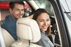 感到愉快在他们新的汽车。坐a的美好的年轻夫妇 免版税库存图片