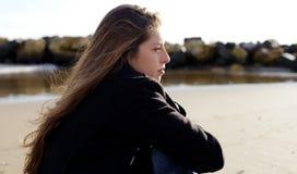 感到沉思的女孩哀伤在海滩前面的冬天 库存照片