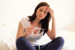 感到的妇女压下和哀伤在看妊娠试验以后 库存图片