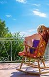感到的阳台的妇女活和在热的夏日释放,看海滩海看法  免版税库存照片