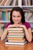 感到确信在她的期终考试前。拿着书和微笑,当站立在图书馆时的快乐的年轻女学生 库存图片