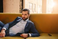 感到确信 在时髦的衣服的放松的英俊的年轻商人在沙发休息在办公室 库存照片