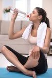 感到渴。体育衣物饮用水的疲乏的少妇 免版税库存照片