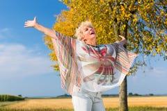 感到活跃资深的妇女自由和愉快,当站立outdoo时 免版税库存图片