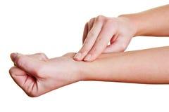 感受脉冲的手指在腕子 免版税库存照片