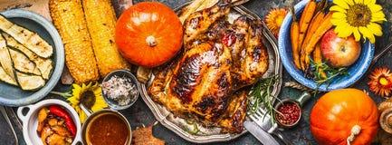感恩天食物 各种各样的烤菜、烤鸡或者火鸡和南瓜与向日葵装饰在黑暗的backgr 免版税库存图片