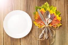 感恩有叉子、刀子和秋叶的菜盘在土气木桌背景 顶视图,拷贝空间 库存照片