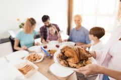 感恩的土耳其 妇女供食她的家庭的一只芳香,可口火鸡在桌上 库存照片